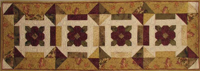 This 16 x 47 inch table runner was created from the DaisyDash #217 pattern by PineTree Lodge Designs. Sewn and quilted by Rita Meyerhoff.